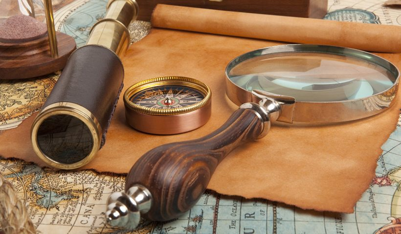 Magnifying glass and compass on a table